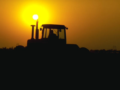 A tractor drives into the sunset