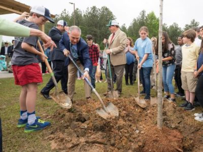 Pruitt plants tree with schoolkids